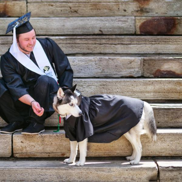 Michael Hasenkamp, a mathematics and computer science degree graduate, poses on the front steps of Old Main with his dog, Luna Lovegood. (Photo by Glenn Asakawa/University of Colorado)
