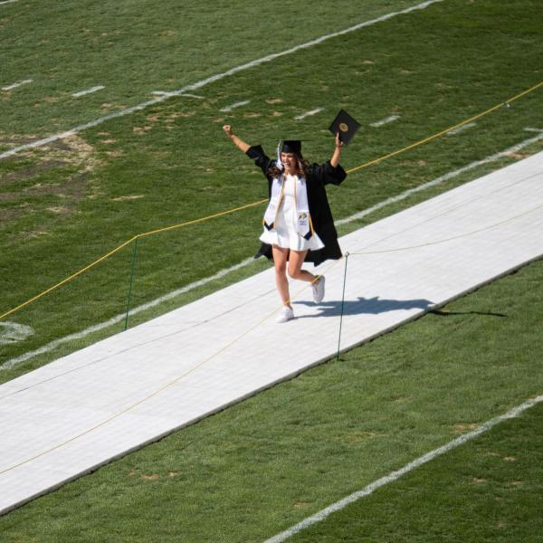 A graduate celebrates after getting her photo taken at Folsom Field during CU Boulder's Graduate Appreciation Days events. (Photo by Glenn Asakawa/University of Colorado)