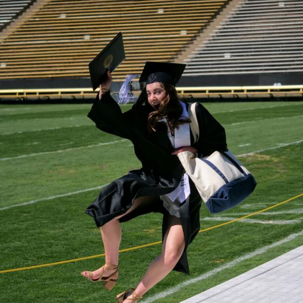Katie Burns kicks up her heels after getting her photo taken at Folsom Field during CU Boulder's Graduate Appreciation Days. (Photo by Glenn Asakawa/University of Colorado)