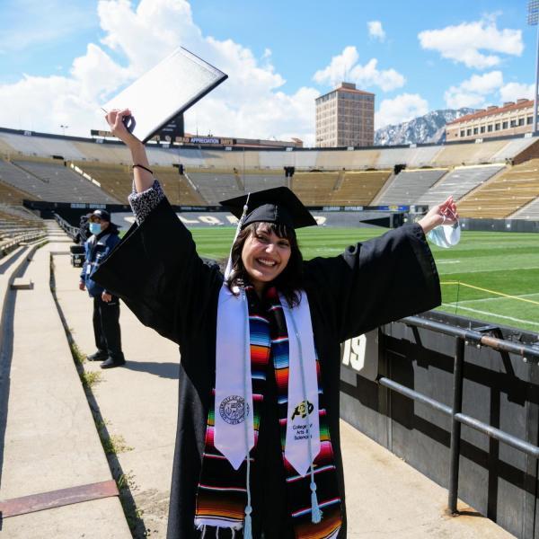 Valeria Ayala Alonso, a molecular biology and psychology double major, celebrates after getting her photo taken at Folsom Field during CU Boulder's Graduate Appreciation Days events. (Photo by Glenn Asakawa/University of Colorado)
