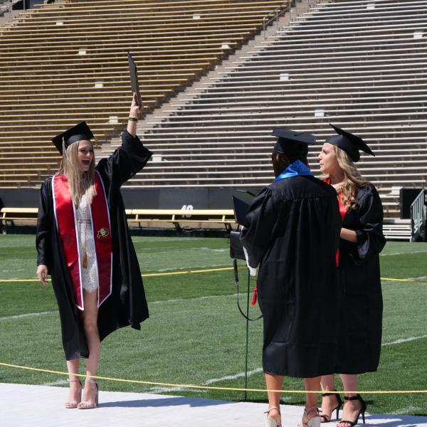 Graduates celebrate after getting their photo taken at Folsom Field during CU Boulder's Graduate Appreciation Days events. (Photo by Glenn Asakawa/University of Colorado)
