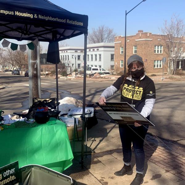 A person at a Campus Housing & Neighborhood Relations booth in a Protect Our Herd T-shirt.