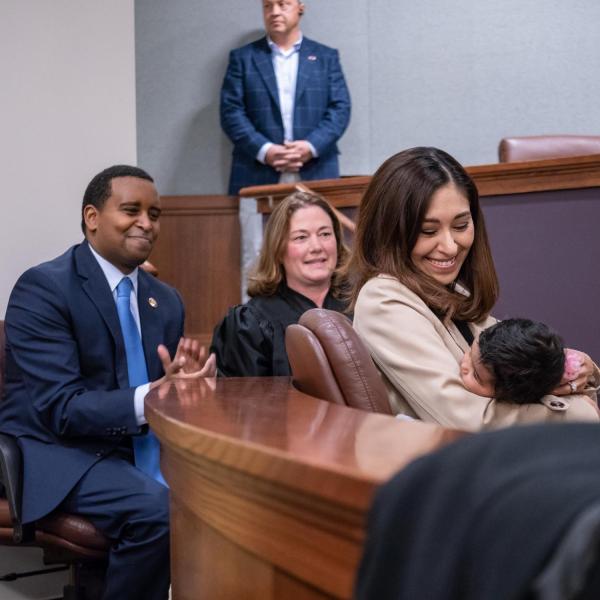 U.S. Representative Joe Neguse and Colorado Supreme Court justice Melissa Hart, center, and Andrea Neguse holding a baby listen to Governor Jared Polis speak. Photo by Glenn Asakawa.