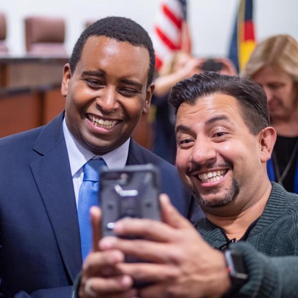 A happy supporter gets a selfie following a ceremonial swearing-in event for U.S. Representative Joe Neguse. Photo by Glenn Asakawa.