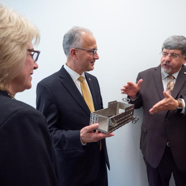 CU President Mark Kennedy, center, holds a magnesium casing for an instrument model that went on mission to Mercury of the Atmospheric and Space Physics (LASP), during a tour of the facility on July 1, 2019, Kennedy's first official day on the job. LASP director of engineering, Tom Sparn, explains how devices are made in-house and Kennedy's wife, Debbie, is at left.