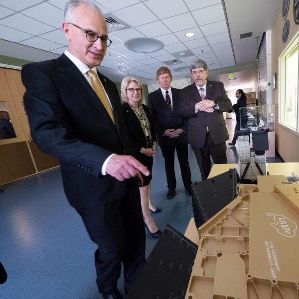 CU President Mark Kennedy, left, points to the CU Boulder athletic logo on a model of a space device during a tour of the CU Boulder's Laboratory for Atmospheric and Space Physics (LASP) on July 1, 2019, Kennedy's first official day on the job. In background: Debbie Kennedy, Mark's wife, LASP director, Dan Baker, and LASP director of engineering, Tom Sparn.