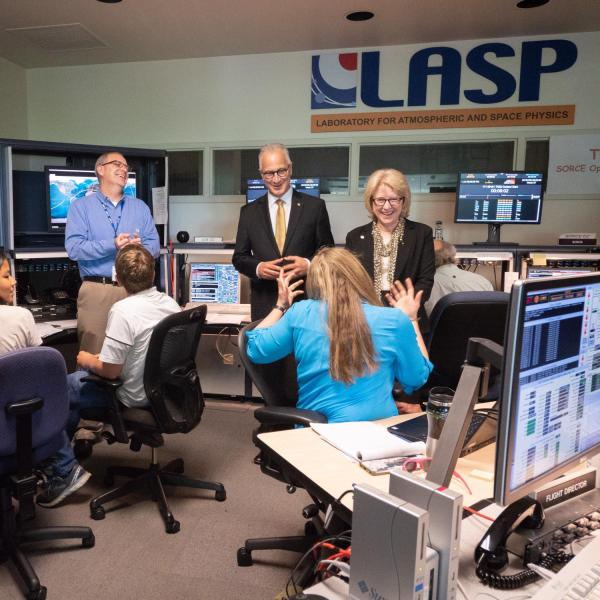 CU President Mark Kennedy, center, and his wife Debbie, share a light moment with students and staff in the control room during a tour of CU Boulder's Laboratory for Atmospheric and Space Physics (LASP) on July 1, 2019, Kennedy's first official day on the job.  Jerry Jason, LASP, director of mission operations and data system, is visible at left. (Photo by Glenn Asakawa/University of Colorado)