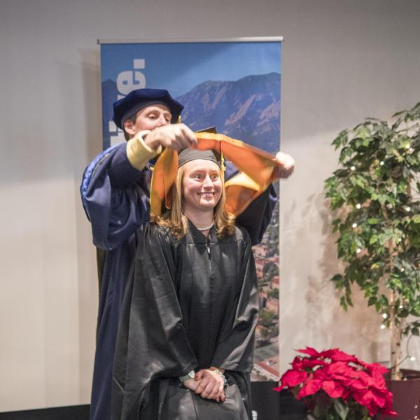 A member of the first graduating class of the Masters of the Environment receives her hooding at recognition ceremony
