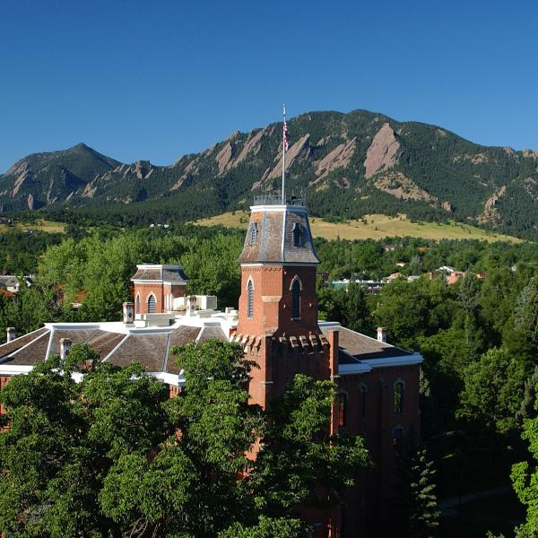 Old Main with green trees, Flatirons in background