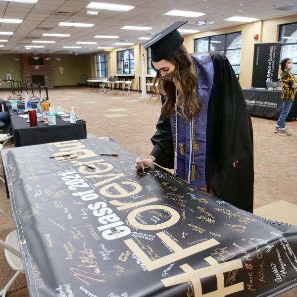 Allie Shea Reuter signs the Class of 2021 banner at the 2021 Graduation Appreciation Days at CU Boulder. (Photo by Casey A. Cass/University of Colorado)
