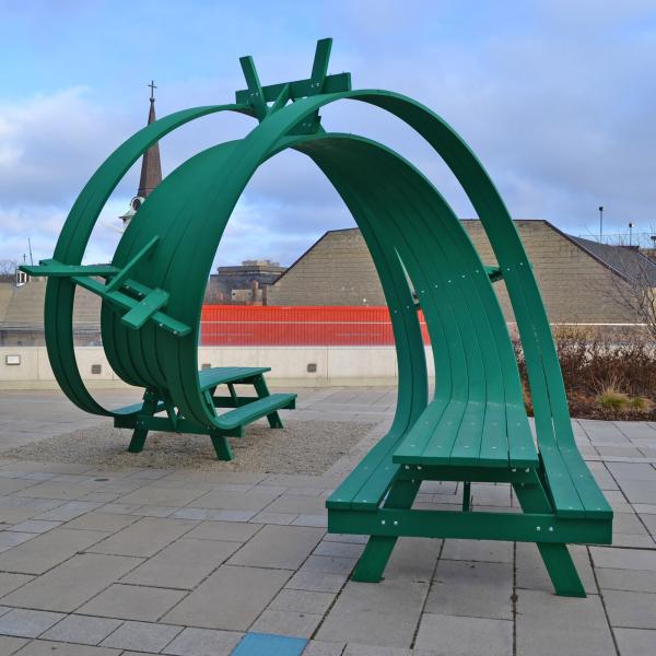 Green picnic table with a roller-coaster like twist