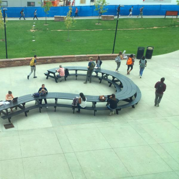 Several people sit at a question-mark-shaped picnic table at the VAC