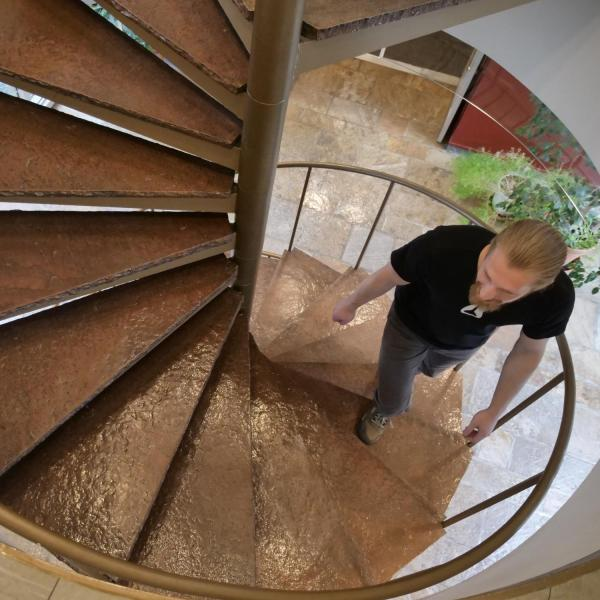 JILA graduate student and teaching assistant Cameron Straatsma climbs the spiral staircase in the JILA building. Photo by Casey A. Cass.