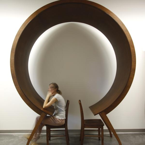Woman sits at and under a unique circular table
