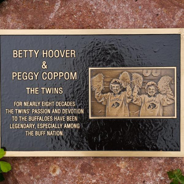 """A plaque honoring the late Betty Hoover and her twins sister, Peggy Coppom, sits between """"twin"""" trees planted along the Buff Walk on the east side of Folsom Field. (Photo by Glenn Asakawa/University of Colorado)"""