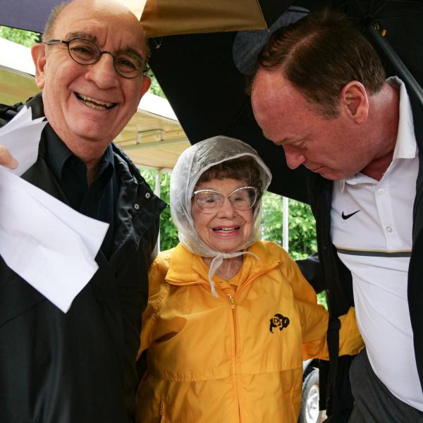 Chancellor Philip DiStefano, left, and Athletic Director Rick George greet Peggy Coppom as they and others gathered on Saturday, June 26, for a tree dedication ceremony honoring Coppom and her late sister Betty Hoover. (Photo by Glenn Asakawa/University of Colorado)