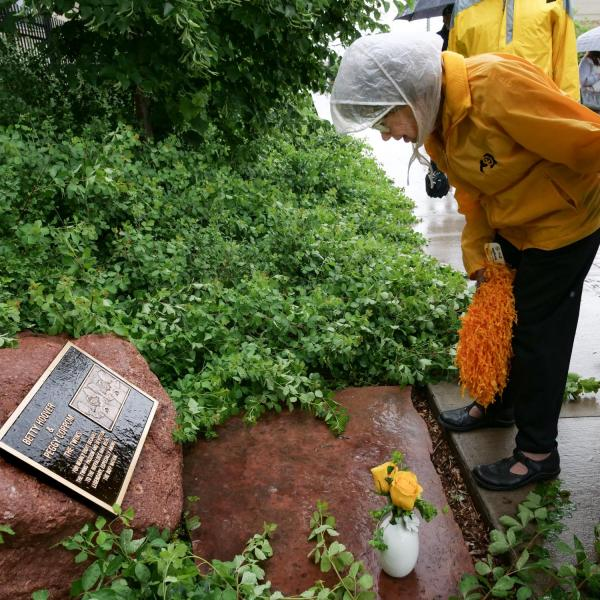 Peggy Coppom looks over a plaque honoring her and her late twin sister, Betty Hoover. (Photo by Glenn Asakawa/University of Colorado)