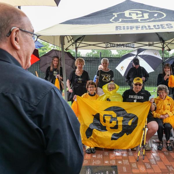 Chancellor Philip DiStefano, left in foreground, Athletic Director Rick George (not visible) and others gathered on June 26 for a tree dedication ceremony honoring CU Buffs super fans Peggy Coppom, seated second from left, and her late sister Betty Hoover. (Photo by Glenn Asakawa/University of Colorado)
