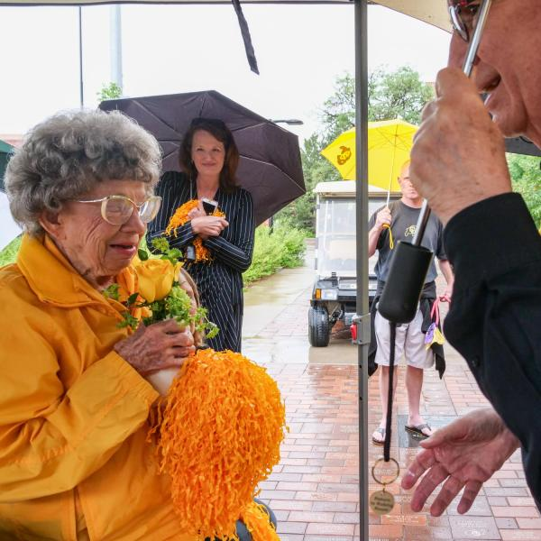 Chancellor Philip DiStefano presents Peggy Coppom with a vase with two yellow roses after he, Athletic Director Rick George and others gathered on Saturday, June 26, for a tree dedication ceremony honoring Coppom and her late sister Betty Hoover. (Photo by Glenn Asakawa/University of Colorado)