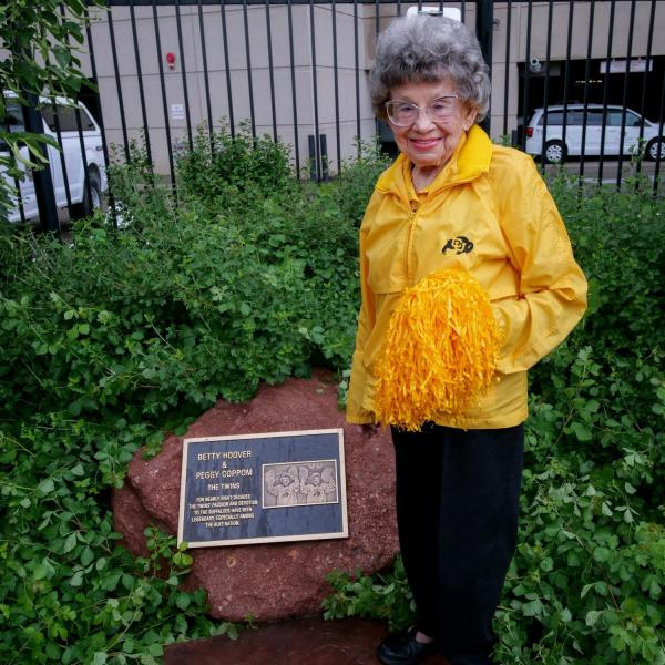 Peggy Coppom stands next to a plaque honoring her and her late twin sister, Betty Hoover. (Photo by Glenn Asakawa/University of Colorado)