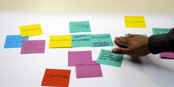 Person arranges sticky notes for session at Diversity and Inclusion Summit