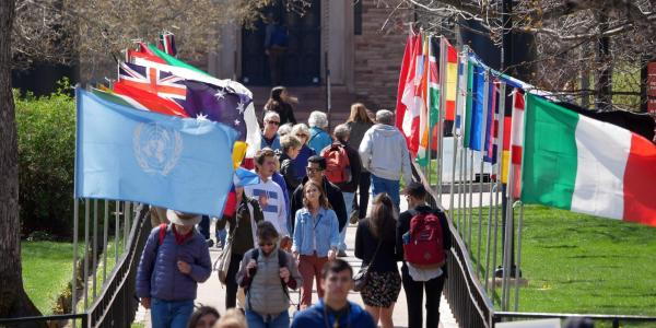 Conference on World Affairs flags fly in the quad. (Photo by Glenn Asakawa/University of Colorado)