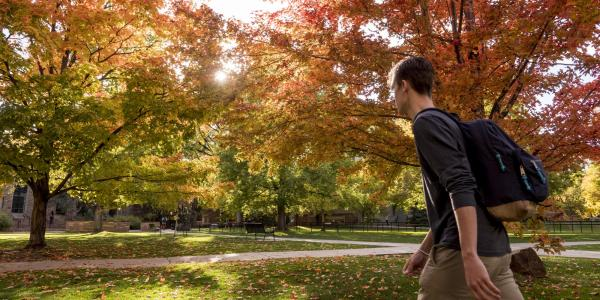 Student walks across campus with fall colors in background