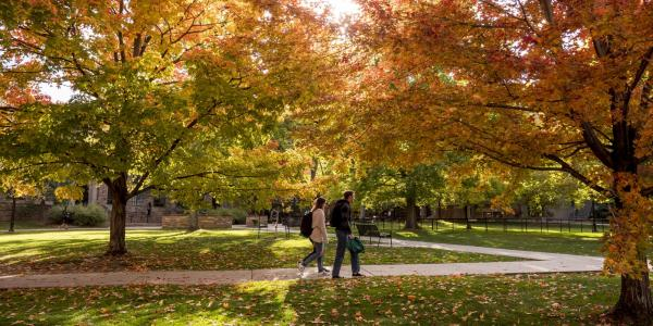 Students walk across campus bursting with fall colors