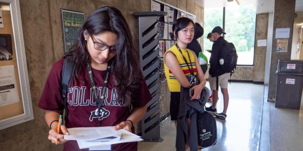 Student looks at orientation paper during Fall Welcome