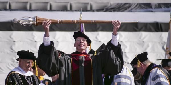 Bud Coleman lifts the ceremonial mace as part of commencement