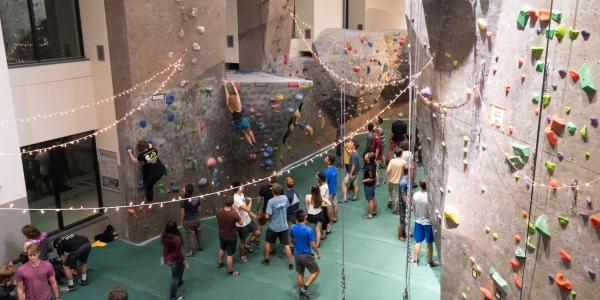 Students hang out by the climbing wall during Connect at The Rec
