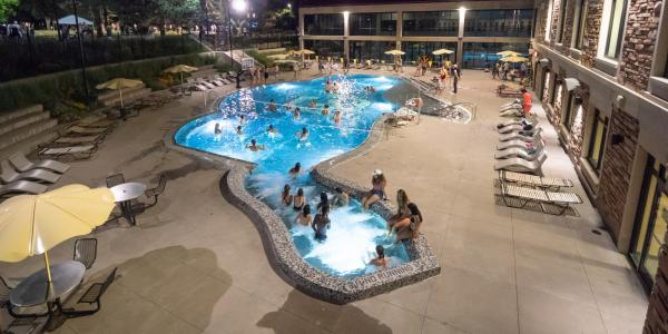 Students swimming in the Buff pool at night