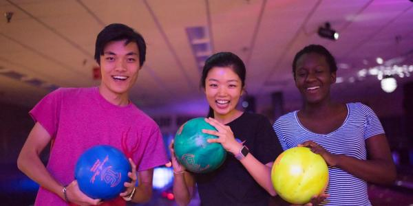 Students pose with bowling balls at The Connection bowling alley