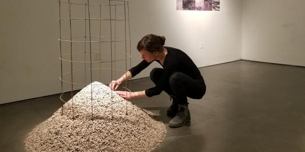 Elspeth Schulze adjusting the wire cage on the granite pile. A collage of vintage postcards of a volcano is on the wall.