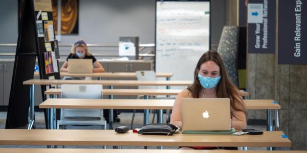 Students in masks studying in the Engineering Lobby.