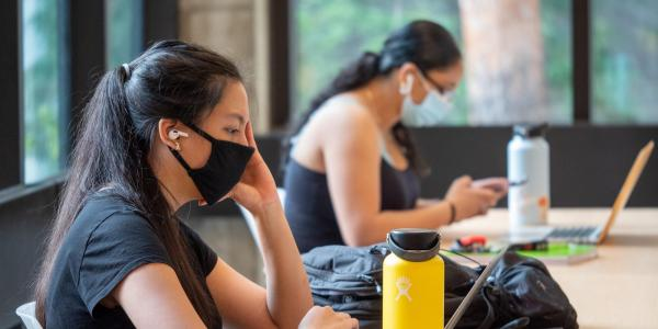 students in masks study inside while physically distancing