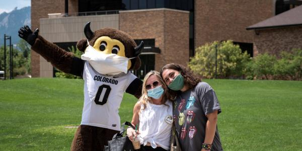 Student and parent pose for a photo with Chip the mascot during move-in