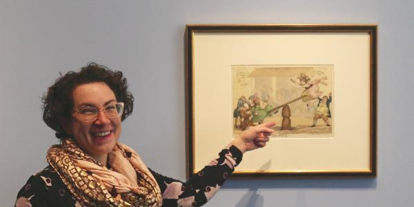 Hope Saska, curator at the CU Art Museum, points to a print from the Bawdy Bodies exhibit