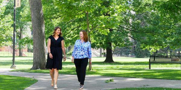 Staff members Alana Davis-Delaria and Eryn Elder walk on campus
