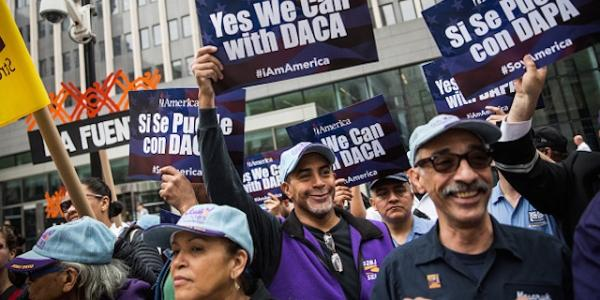 """Activists hold up signs that say """"Yes We Can with DACA"""" in English and Spanish"""