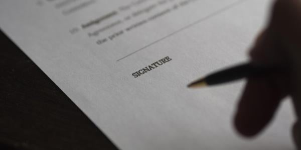 Person holds pen above contract