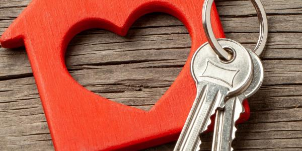 Stock image of keys on a keychain shaped like a house with a heart inside of it