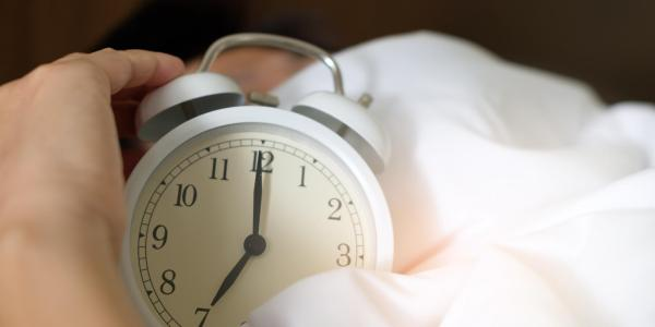 person in bed turns off an alarm clock