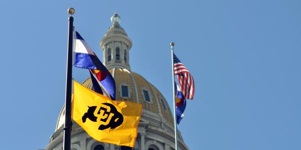 Several flags -- CU's, the state of Colorado's and the United State's -- are raised near the Colorado state capitol.