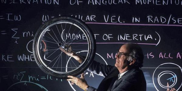 Professor Albert Bartlett holds up bicycle wheel in classroom