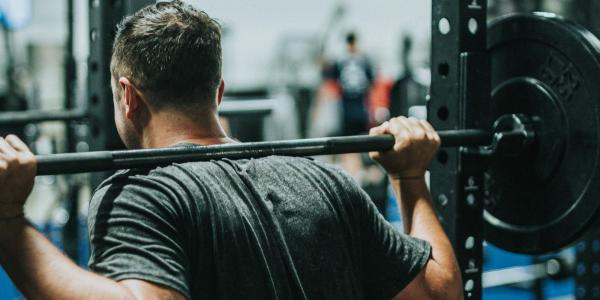 "A person lifting a barbell (Photo by Andrew ""Donovan"" Valdivia/Unsplash)"