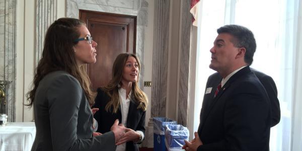 """2016 AAAS """"CASE"""" workshop competition winners Angela Boag and Sarah Welsh-Huggins speaking with U.S. Senator Cory Gardner."""