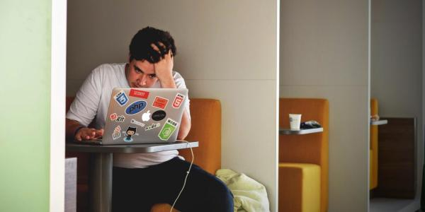 Person sits at table with computer, stressed out