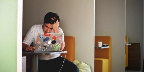 Stressed out student works at computer