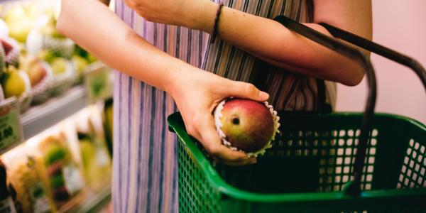 Woman puts red apple into her grocery shopping basket